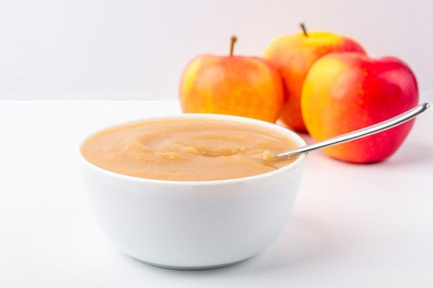 Compota de maçã caseira fresca. o conceito de nutrição adequada e alimentação saudável. comida orgânica e vegetariana. bacia branca com purê de frutas na tela e corte as maçãs na mesa. copie o espaço para texto