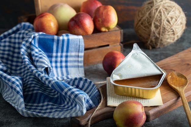 Compota doce com pêssegos e colher de pau na placa de madeira
