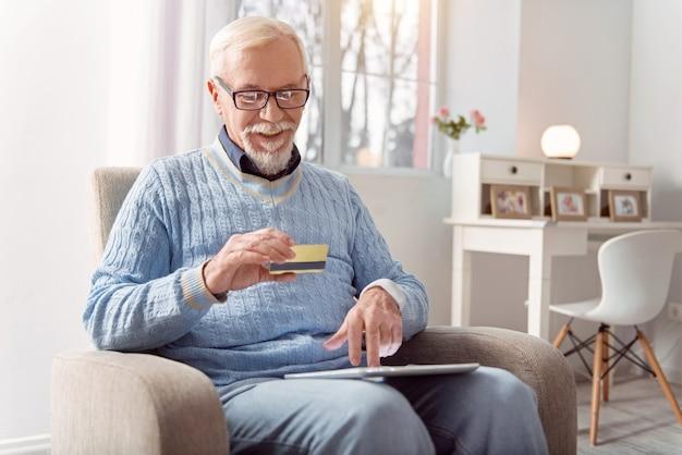 Compra conveniente. ancião encantador sentado na poltrona e usando seu cartão dourado do banco enquanto paga suas compras online