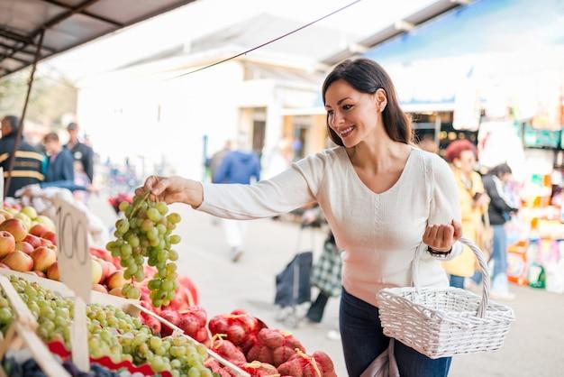 Compra da jovem mulher no mercado local do alimento.