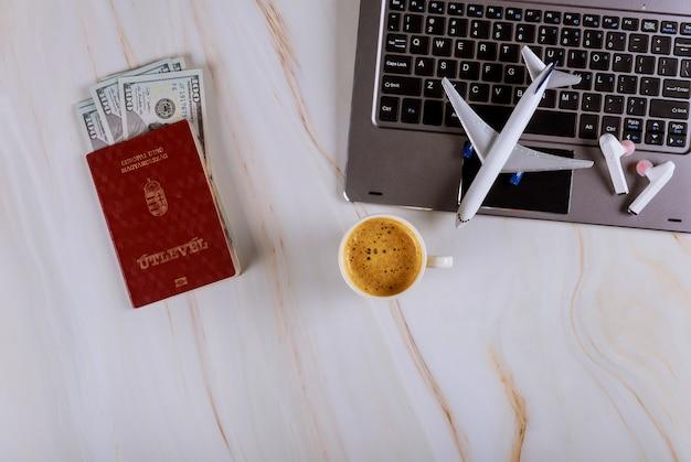 Compra de bilhetes on-line em reservas de avião com computador, passaportes húngaros e notas de dólar