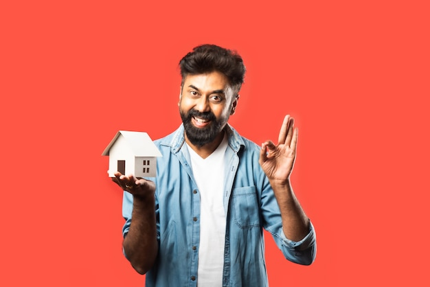 Compra de imóveis e conceito de pessoas. homem barbudo indiano com modelo de casa em miniatura, chaves e cofrinho em vermelho