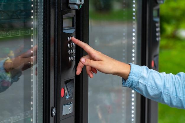 Compra de refrigerantes e doces em uma máquina de venda automática na rua durante um passeio pela cidade