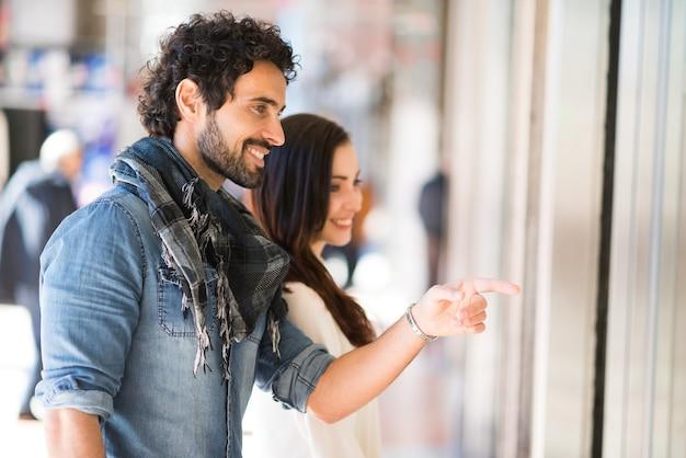 Compra de sorriso nova dos pares em uma rua urbana. profundidade de campo rasa, foco no homem