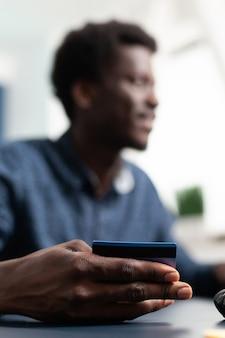 Compra do consumidor de transação online com cartão de crédito, introduzindo dados de pagamento african american man ma ...