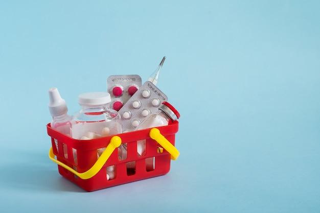 Compra e conceito de medicina compras on-line. várias cápsulas, comprimidos e medicamento no cesto de compras em fundo azul.