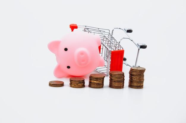Compra inteligente e economiza o conceito de dinheiro. carrinho de compras caído, moeda e cofrinho em branco.