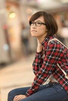 Compra jovem de asiático sentar no banco do shopping em taipei, taiwan.