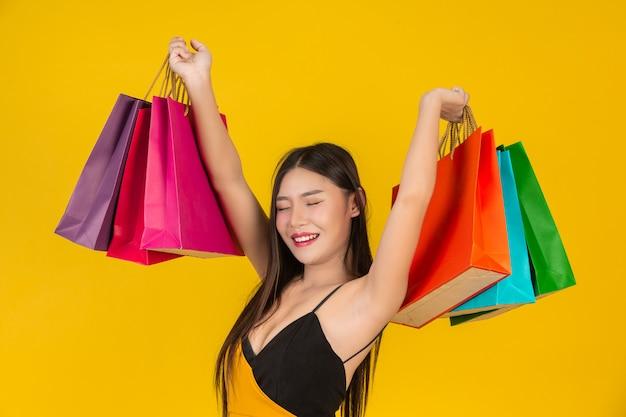 Compra linda mulher segurando um saco de papel colorido em um amarelo.