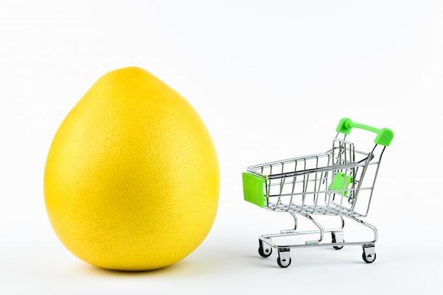 Compra o conceito de negociação de pomelo. loja online. cesta e pomelo em um branco. conceito de alimentação saudável conceito de negócio