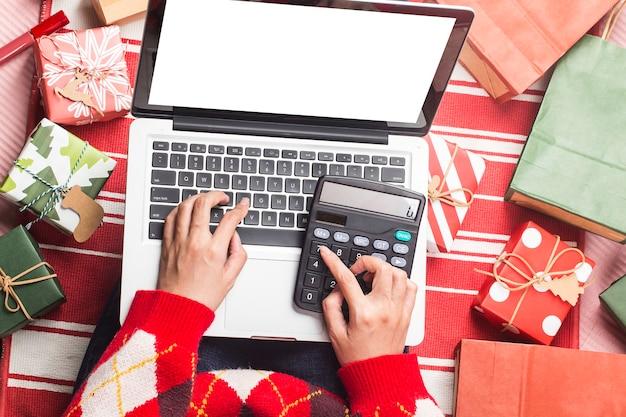 Compra online de natal compradora com laptop prepara-se para a véspera de natal