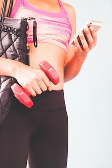 Compra online de telefonia inteligente na mão da mulher. vestuário de fitness no fundo do clube desportivo. compre itens de esporte com site de comércio eletrônico