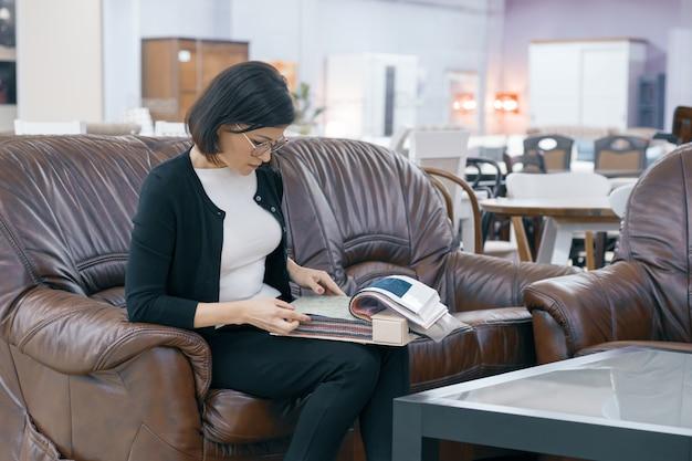 Comprador de mulher adulta, olhando para um livro com tecidos para estofados