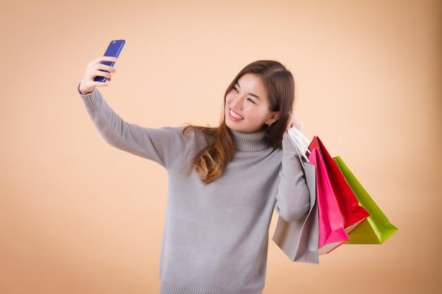 Comprador de mulher com sacos e tomar selfie