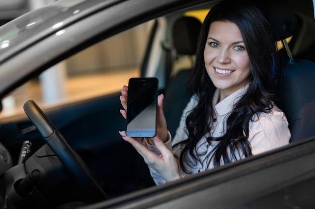 Comprador de mulher feliz examina seu novo veículo na concessionária