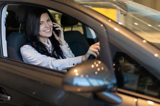Comprador de mulher feliz sentado em seu novo veículo na concessionária