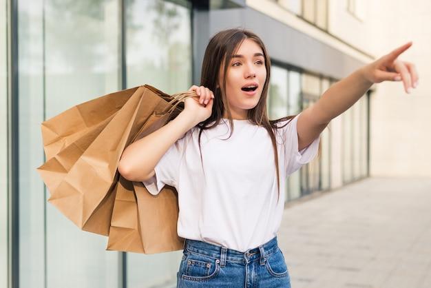 Comprador espantado abrindo a boca segurando sacolas de compras, vendo ofertas especiais em lojas e apontando na rua