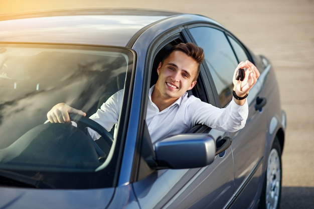 Comprador feliz segurando as chaves do carro dentro de seu novo veículo