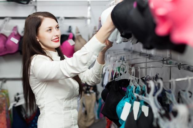 Comprador fêmea que escolhe sutiã na loja de roupa