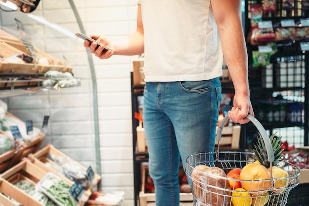 Comprador masculino com cesta e telefone celular nas mãos, cliente no mercado. compras em loja de alimentos