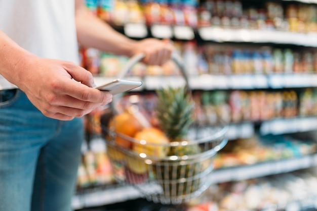 Comprador masculino em mãos com cesta de frutas e telefone