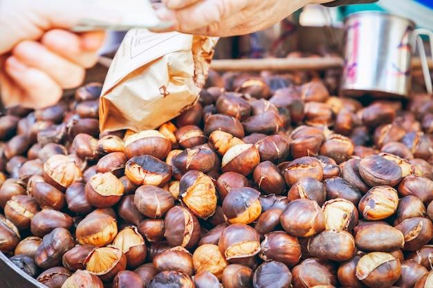 Comprador paga por castanhas grelhadas a carvão no mercado de alimentos de outono