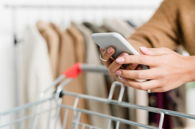 Compradora com as mãos segurando um smartphone enquanto rola e empurra o carrinho durante a visita à boutique no período de venda sazonal
