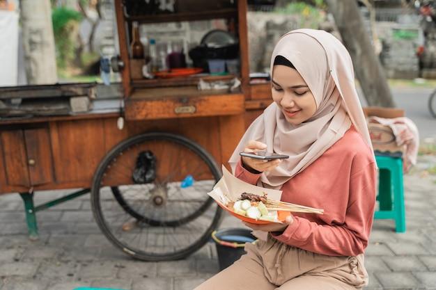 Compradora de frango satay tirando foto de sua comida usando um telefone inteligente