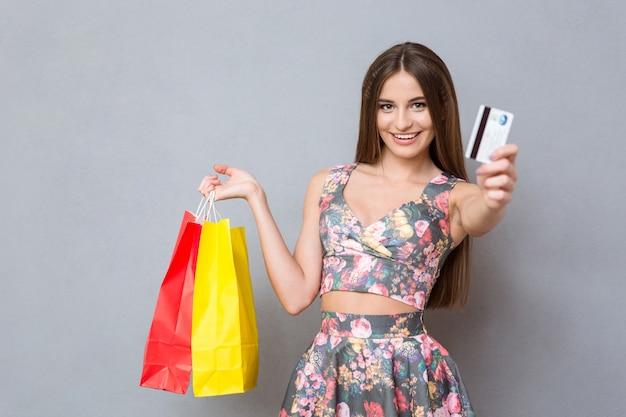 Compradora feliz, muito animada, com cabelo comprido, mostrando um cartão de crédito, segurando sacolas coloridas e sorrindo