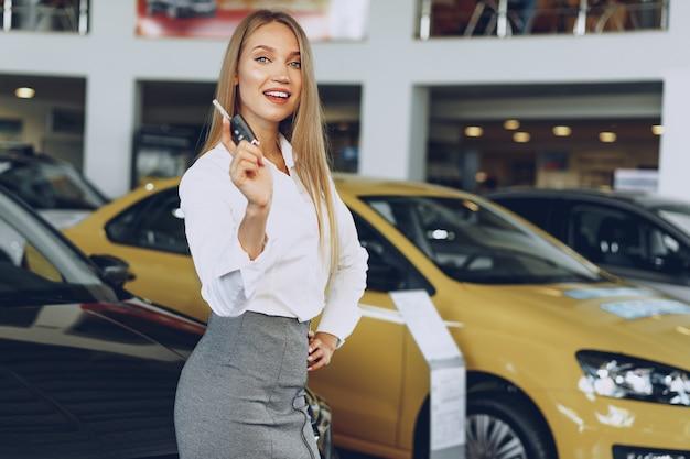 Compradora ou vendedora jovem feliz perto do carro com as chaves na mão.