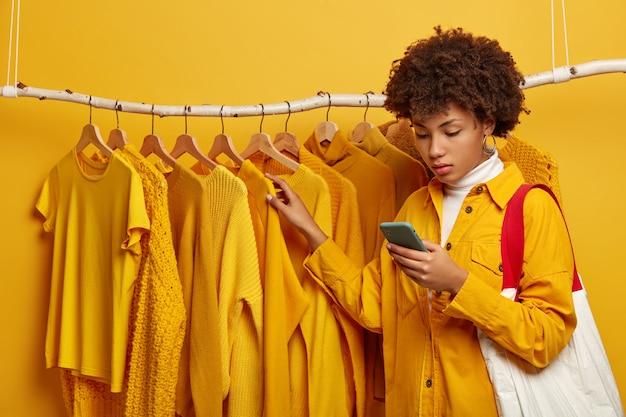 Compradora séria de cabelos cacheados carrega bolsa, pega roupas amarelas, concentrada em smartphone, posa perto de uma prateleira de roupas elegantes, faz compras