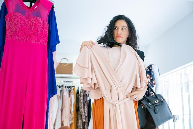 Compradora séria segurando cabide com pano, aplicando o vestido para si mesma, olhando para longe. vista frontal. loja de moda ou conceito de varejo