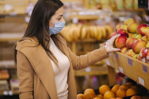Compradora usando uma máscara protetora e luvas no supermercado. compras durante a quarentena pandêmica. mulher comprando frutas frescas