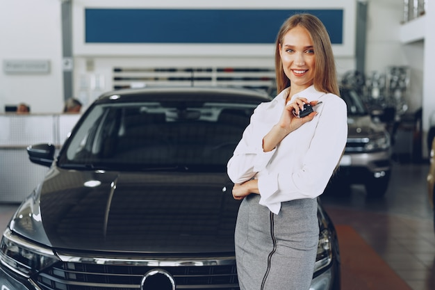 Compradora / vendedora jovem feliz perto do carro com as chaves na mão