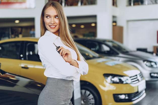 Compradora / vendedora jovem feliz perto do carro com as chaves na mão.