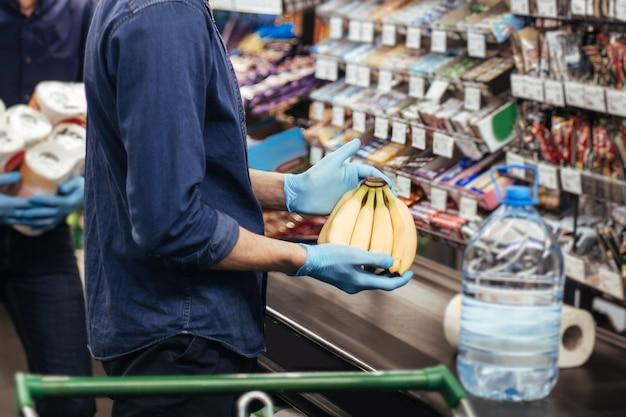 Compradores com máscaras de proteção em pé perto do caixa em um supermercado