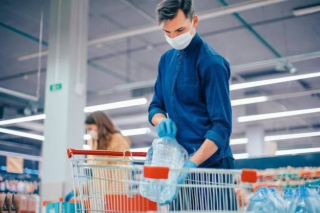 Compradores com máscaras de proteção escolhendo produtos no supermercado