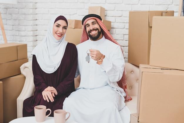 Compradores de casas árabes ricos perto de caixas de embalagem.
