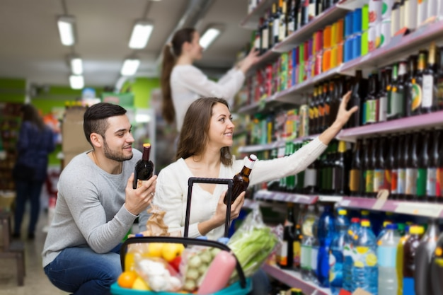 Compradores que escolhem garrafa de vinho na loja de licores