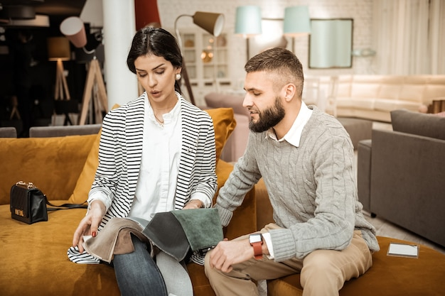 Comprando peças caseiras. mulher interessada separando pedaços do material do sofá enquanto o marido barbudo a apoia