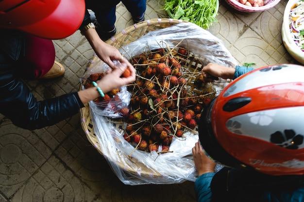 Comprando rambutans no mercado asiático