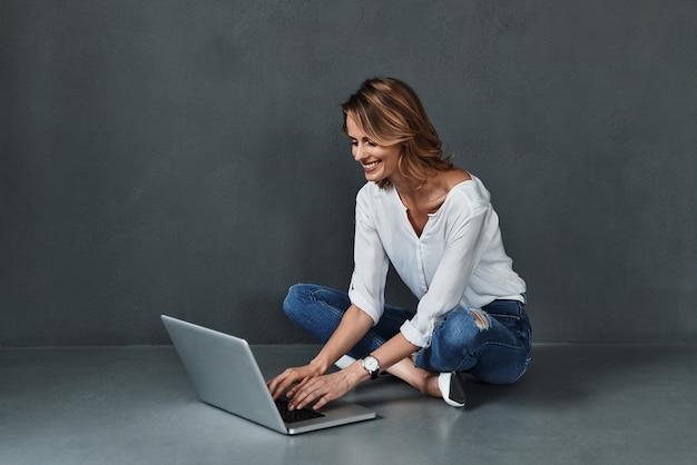 Comprar online. mulher jovem e atraente no casual wear usando o computador e sorrindo enquanto está sentado no chão contra um fundo cinza