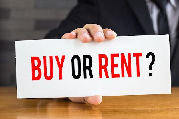 Comprar ou alugar, mensagem em cartão branco e segure pelo empresário
