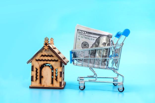 Comprar uma casa e um imóvel, vender uma casa, conceito de negócio imobiliário, casa nova em um carrinho e dólares em uma mesa azul.