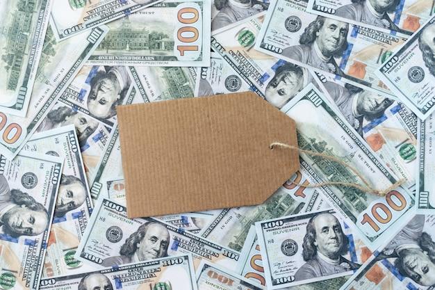 Compras banner maquete com etiqueta de papelão no fundo de notas de dinheiro de dólar