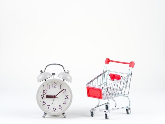 Compras conceito de carrinho e relógio analógico no fundo branco