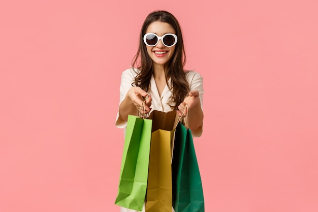 Compras, conceito de consumidor. alegre menina morena atraente, segurando sacolas de compras e sorrindo, usando óculos, desfrutando de navegar pelas bancas da loja, rosa alegre