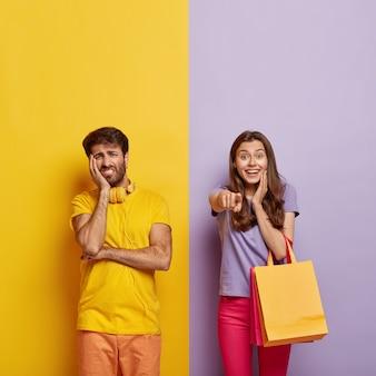 Compras, consumismo, conceito de venda. mulher viciada em compras segura sacolas de compras e aponta para um item com desconto na loja