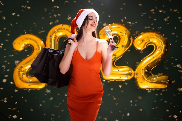Compras de ano novo mulher com balões de ar pretos sexta-feira com champanhe e compras comemoram