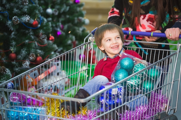 Compras de ano novo. uma criança está fazendo compras no supermercado com os pais.